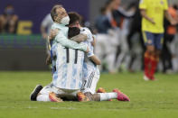 Argentina's players Angel Di Maria, center, and Rodrigo De Paul, right, embrace a member of the team after defeating Colombia in a penalty shootout during a Copa America semifinal soccer match at the National stadium in Brasilia, Brazil, Wednesday, July 7, 2021. (AP Photo/Eraldo Peres)