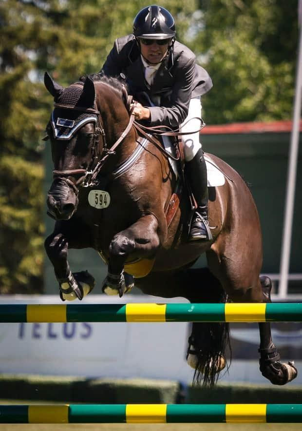 Canada's Brian Morton, pictured in 2016 riding Atlantis, stood atop the leaderboard alongside Ireland's Jordan Coyle following a jump-off. (Jeff McIntosh/The Canadian Press - image credit)