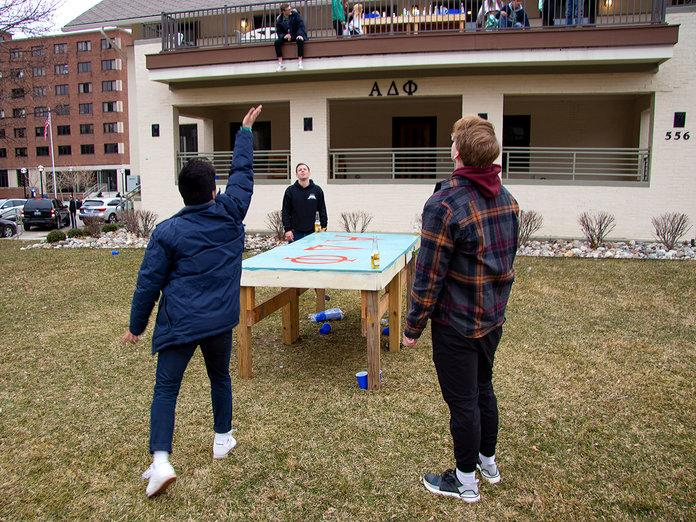 U of M students Tom Pavey, Brandon Pham, Drew Hirselj, and Owen Hill play a drinking game outside of their fraternity house. | Asha Lewis