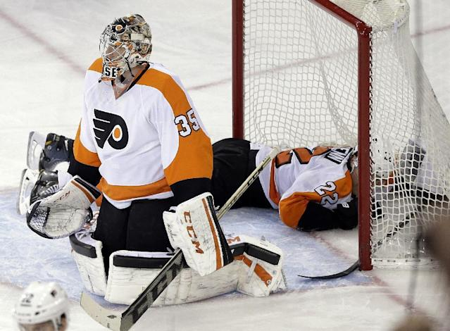 Philadelphia Flyers goalie Steve Mason (35) and teammate Luke Schenn (22) react after New York Rangers' Dominic Moore scored a goal during the third period of an NHL hockey game Wednesday, March 26, 2014, in New York. The Rangers won 3-1. (AP Photo/Frank Franklin II)