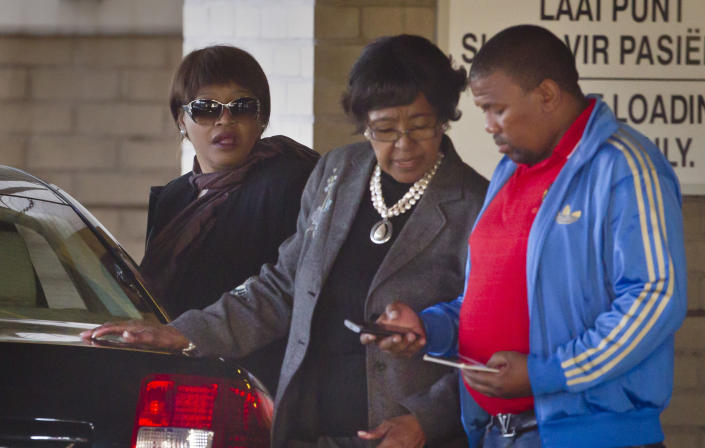 <p>Former wife Winnie Madikizela-Mandela, center, and daughter Zindzi Mandela, left, leave the Mediclinic Heart Hospital where former South African President Nelson Mandela was being treated in Pretoria, South Africa, on June 14, 2013. (Photo: Ben Curtis/AP) </p>