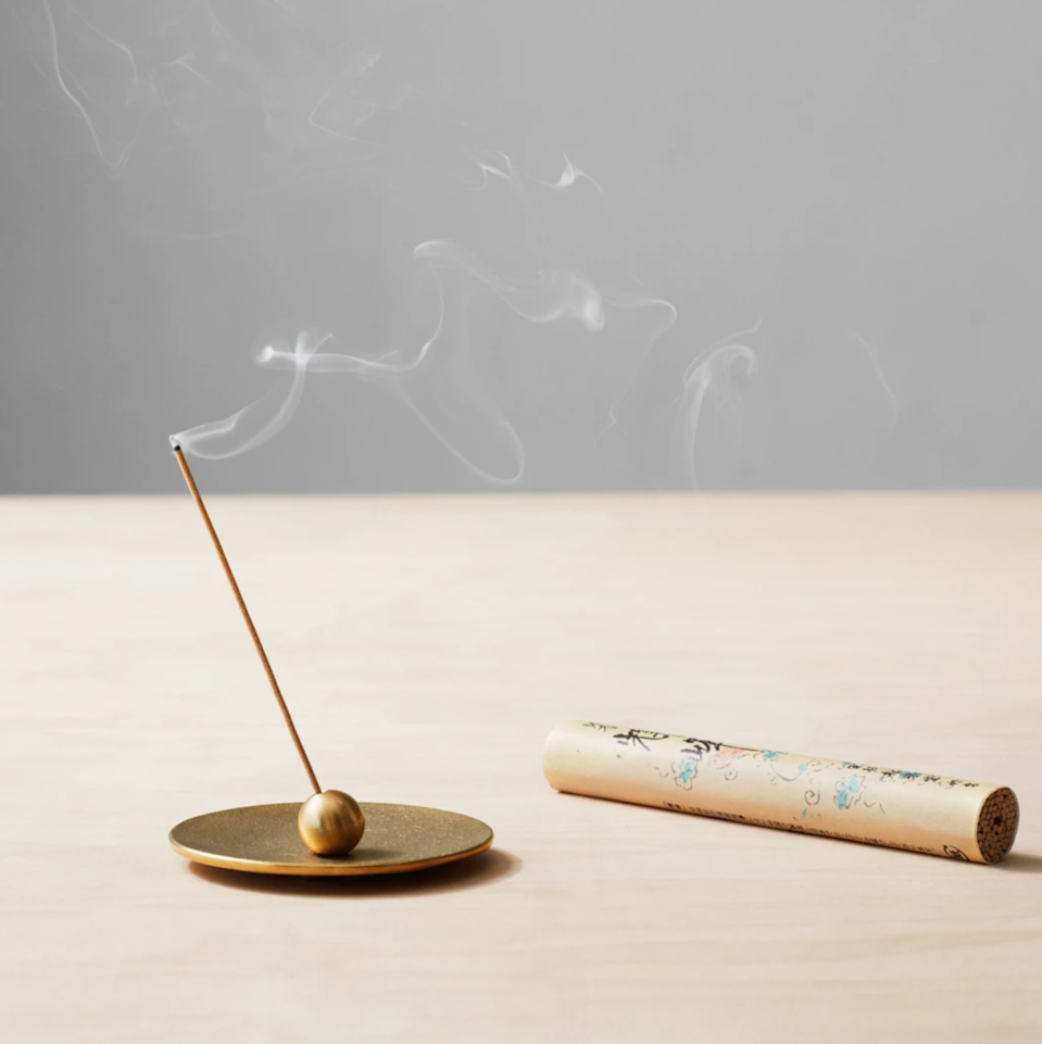 """File this incense set under """"things they'd love, but wouldn't buy for themselves."""" Handcrafted in Japan by The Takaoka Casting Workshop, each brass holder comes with 100 sandalwood incense sticks. $75, The Citizenry. <a href=""""https://www.the-citizenry.com/products/brass-incense-holder?variant=20226244804681"""" rel=""""nofollow noopener"""" target=""""_blank"""" data-ylk=""""slk:Get it now!"""" class=""""link rapid-noclick-resp"""">Get it now!</a>"""