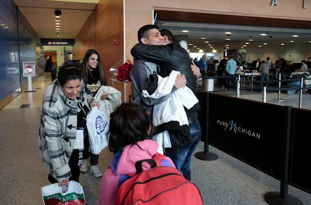 Rami Al-Qassab, at right, hugs his brother after being reunited with his Iraqi refugee mother Amira, left, and siblings after they arrived at Detroit Metro Airport in Romulus, Michigan, Feb. 10, 2017. (Rebecca Cook / Reuters)