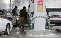 People fill their gas tank at a gas station in Chicago, Friday, Jan. 3, 2014. The snowstorm may finally have left town but a winter weather advisory is in effect for this evening when southerly winds are expected to kick up blizzard-like conditions. (AP Photo/Nam Y. Huh)