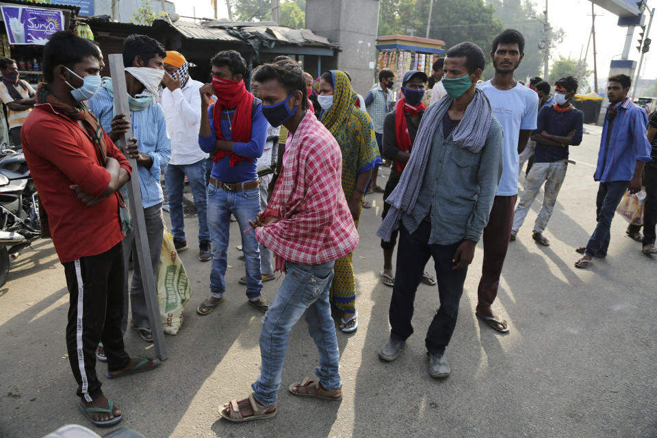 Migrant laborers from other states stand on a street looking for work on the outskirts of Jammu, India, Sunday, Sept.27, 2020. The nation of 1.3 billion people is expected to become the coronavirus pandemic's worst-hit country within weeks, surpassing the United States. (AP Photo/Channi Anand)