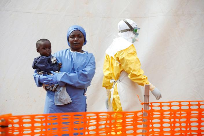 Mwamini Kahindo, an Ebola survivor working as a caregiver to babies who are confirmed Ebola cases, holds an infant outside the red zone at the Ebola treatment center in Butembo, Democratic Republic of Congo, March 25, 2019. (Photo: Baz Ratner/Reuters)