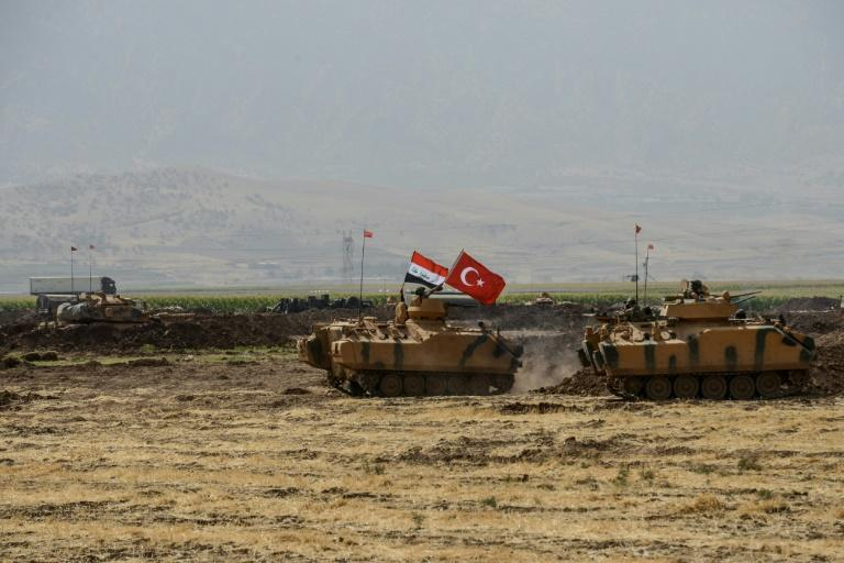 Soldiers drive tanks bearing Turkish and Iraqi flags during a joint military exercise near the Turkish-Iraqi border at Silopi district in Sirnak on September 26, 2017