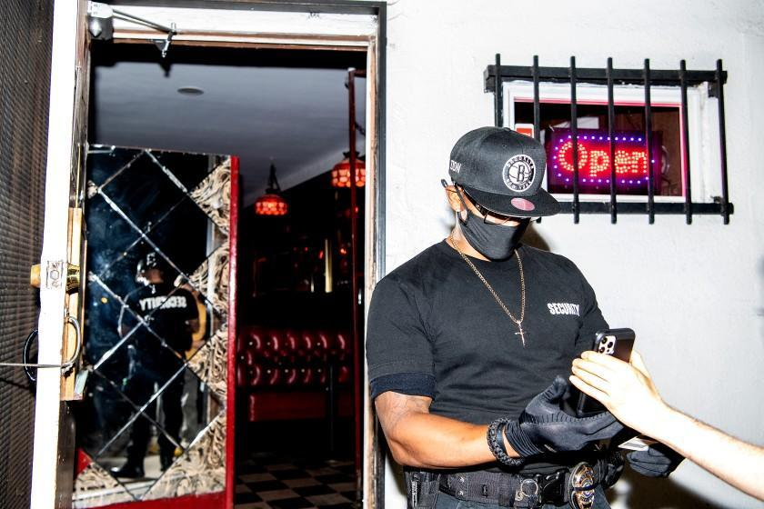 LOS ANGELES, CA - JULY 30: Security officer Don McClaren checks for proof of vaccination status from customers before they can enter the bar inside Permanent Records Roadhouse on Friday, July 30, 2021 in Los Angeles, CA. (Mariah Tauger / Los Angeles Times)