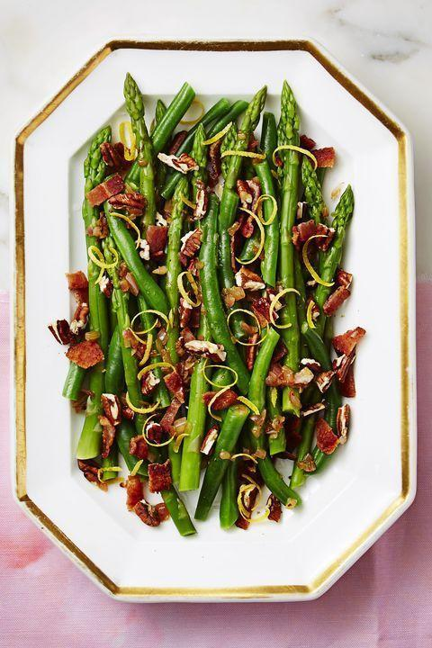 """<p>Shallots and lemon add a zesty note to these hearty veggies, while chopped pecans come with a punch of earthy warmth to round out your bite. </p><p><strong>RELATED</strong>: <a href=""""https://www.goodhousekeeping.com/food-recipes/cooking/g19746678/how-to-cook-asparagus/"""" rel=""""nofollow noopener"""" target=""""_blank"""" data-ylk=""""slk:How to Make the Best Asparagus Ever"""" class=""""link rapid-noclick-resp"""">How to Make the Best Asparagus Ever</a></p><p><em><em><a href=""""https://www.goodhousekeeping.com/food-recipes/a37456/nutty-green-beans-and-asparagus-with-bacon-recipe/"""" rel=""""nofollow noopener"""" target=""""_blank"""" data-ylk=""""slk:Get the recipe for Nutty Green Beans and Asparagus With Bacon"""" class=""""link rapid-noclick-resp"""">Get the recipe for Nutty Green Beans and Asparagus With Bacon</a> <em><em>»</em></em></em></em></p>"""
