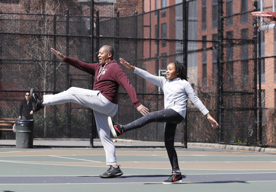 """FILE - Fred Frazer, a property manager, exercises with his daughter Olivia, 10, on the Christopher """"Biggie"""" Wallace basketball courts in the Brooklyn borough of New York, in this Thursday, March 26, 2020, file photo. During the pandemic, people around the world sought relief from lock downs and working from home in leisure sports. (AP Photo/Kathy Willens, File)"""