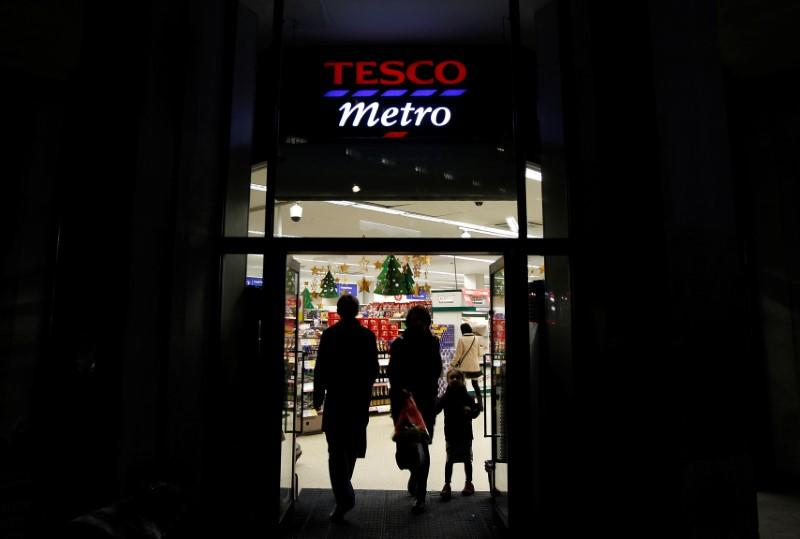 Customers enter and exit a Tesco shop in London