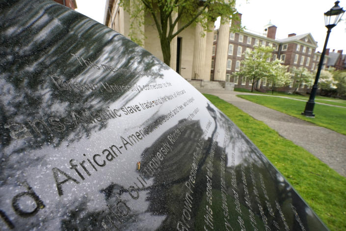 """Words engraved on a stone plinth form a component of the Slavery Memorial by sculptor Martin Puryear, erected in 2014, on the Brown University campus in Providence, R.I., on Tuesday, May 4, 2021. An """"Anti-Black Racism"""" task force is expected to deliver recommendations soon for how the school can further promote racial equity. But university spokesperson Brian Clark stressed it's not clear whether the panel, which was formed during last summer's racial unrest, will address reparations. (AP Photo/Steven Senne)"""