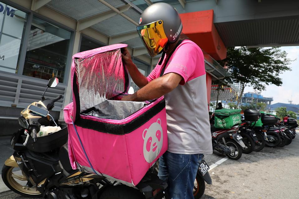 FILE PHOTO: A Foodpanda rider gets ready for a delivery outside a shopping mall, amid the coronavirus disease (COVID-19) outbreak in Kuala Lumpur, Malaysia May 28, 2020. (Source: REUTERS/ Lim Huey Teng)