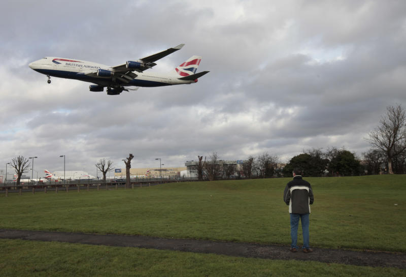 FILE - A man watches as a British Airways plane lands at London's Heathrow Airport, in this Monday Jan. 10, 2011 photo. More pollution is likely to mean bumpier flights for trans-Atlantic travelers, researchers say, predicting increased turbulence over the north Atlantic as carbon dioxide levels rise.  (AP Photo/Lefteris Pitarakis, file)