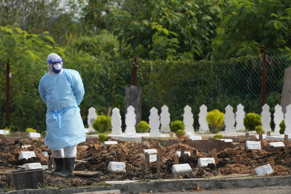 A health worker wearing Personal Protective Equipment (PPE) stands during a funeral procession for COVID-19 victims at a Muslim cemetery on the outskirts of Klang, Malaysia, Friday, Aug. 27, 2021. Malaysia hit a daily record of coronavirus infections on Thursday. (AP Photo/Vincent Thian)