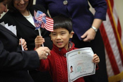 Born in China, Zachary Shields, 6, holds up his citizenship certificate during a 2011 citizenship ceremony