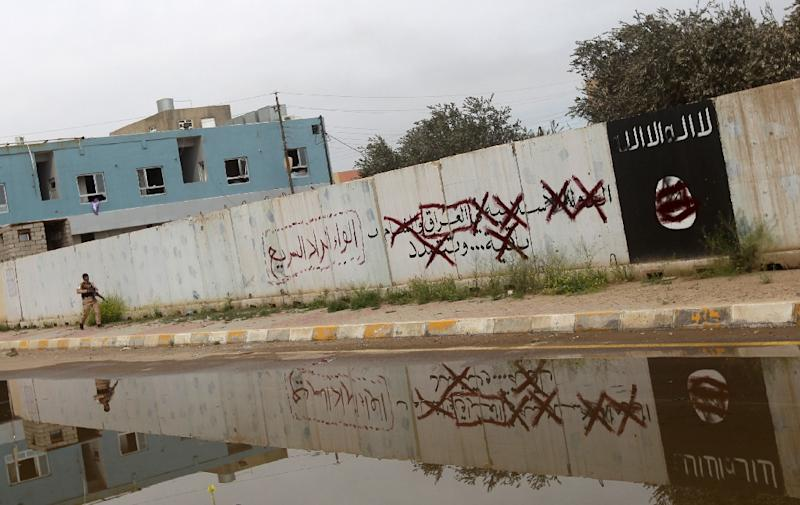 A Shiite fighter from the Popular Mobilisation units walks down an alley bearing defaced Islamist slogans and emblems, in Tikrit on April 1, 2015 (AFP Photo/Ahmad al-Rubaye)