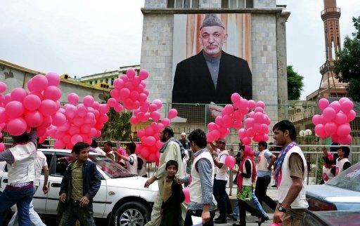 Volunteers walk past a poster of Afghan President Hamid Karzai, in Kabul, on May 25, 2013