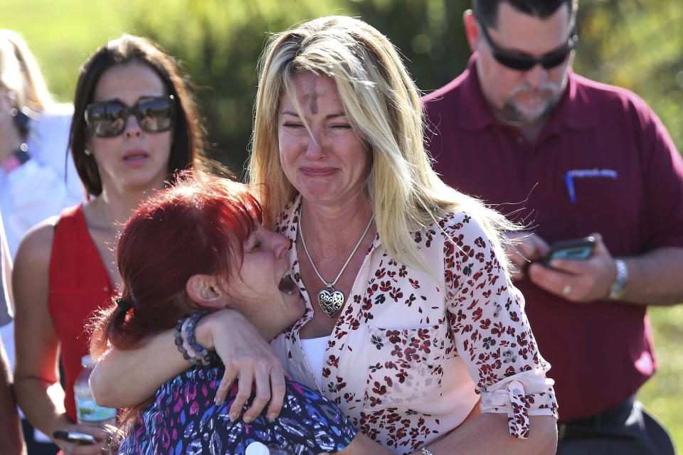 FILE - In this Feb. 14, 2018 file photo, parents wait for news after a report of a shooting at Marjory Stoneman Douglas High School in Parkland, Fla. Sorrow is reverberating across the country Sunday, Feb. 14, 2021, as Americans joined a Florida community in remembering the 17 lives lost three years ago in the Parkland school shooting massacre. President Joe Biden used the the occasion to call on Congress to strengthen gun laws, including requiring background checks on all gun sales and banning assault weapons. (AP Photo/Joel Auerbach, File)