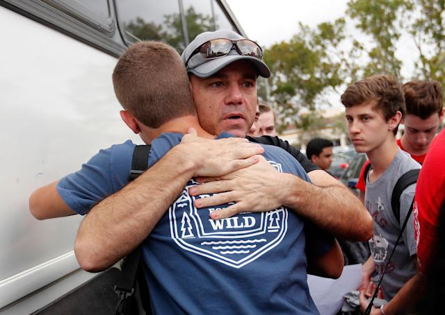 <p>Tom Carmo, father of survivor Ethan Rocha, hugs student Joey Cordova, as students from Stoneman Douglas High School board buses in Parkland, Fla., Tuesday, Feb. 20, 2018. The students plan to hold a rally Wednesday in hopes that it will put pressure on the state's Republican-controlled Legislature to consider a sweeping package of gun-control laws, something some GOP lawmakers said Monday they would consider. (Photo: Gerald Herbert/AP) </p>