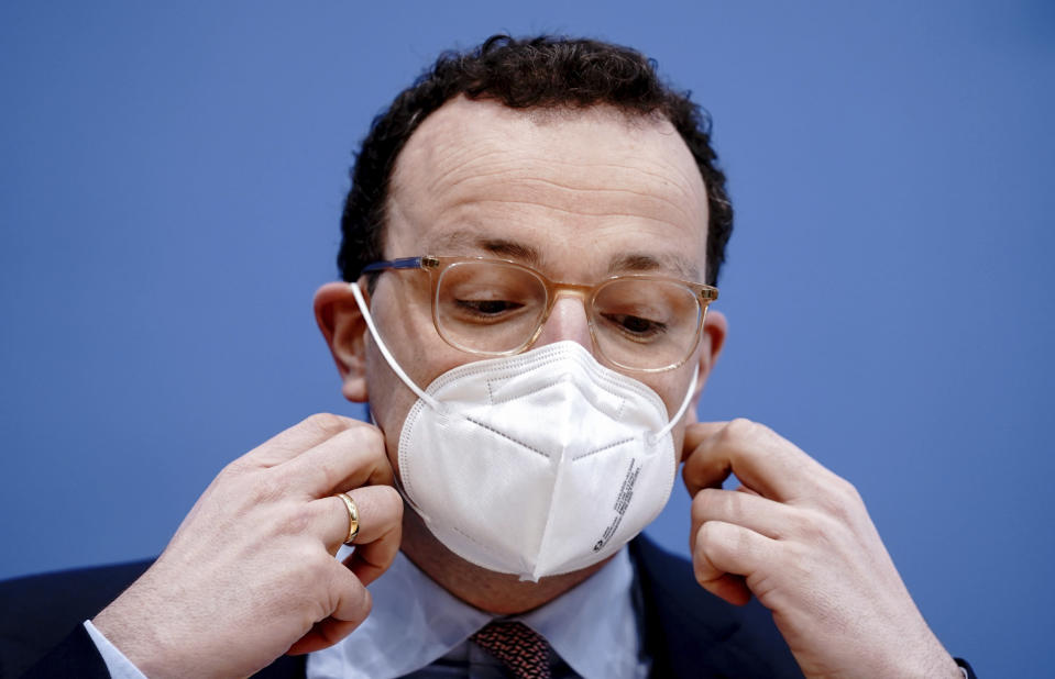 German Health Minister Jens Spahn takes off his FFP2 mask as he attends at a news conference on the Germany's current situation in the Coronavirus pandemic at the Federal Press Conference in Berlin, Germany, Friday, Jan. 29, 2021. (Kay Nietfeld/dpa via AP)