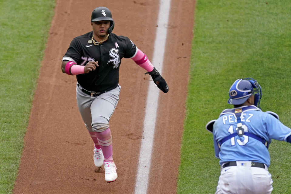 Chicago White Sox's Yermin Mercedes runs home past Kansas City Royals catcher Salvador Perez to score on a sacrifice fly hit by Leury Garcia during the second inning of a baseball game Sunday, May 9, 2021, in Kansas City, Mo. (AP Photo/Charlie Riedel)