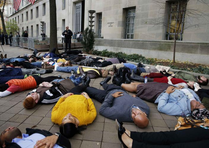 """Protestors stage a """"die-in"""" as they rally against the Ferguson, Mo. Grand Jury exoneration of police officer Darren Wilson for his August 2014 shooting and killing of Michael Brown while, at the U.S. Justice Department in Washington, December 1, 2014. U.S. President Barack Obama asked Congress on Monday for $263 million for the federal response to the civil rights upheaval in Ferguson, Missouri, and is setting up a task force to study how to improve modern-day policing. REUTERS/Larry Downing (UNITED STATES - Tags: POLITICS CIVIL UNREST CRIME LAW SOCIETY)"""