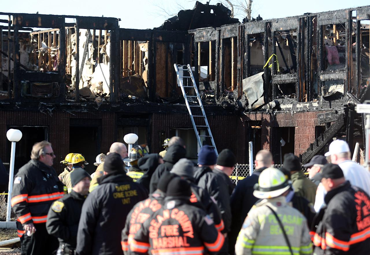 Firefighters investigate an early morning fire at the Mariner's Cove Hotel in Point Pleasant Beach, N.J. on Friday, March 21, 2014. An early morning fire killed three people at the Jersey shore motel whose residents included Superstorm Sandy victims who were staying there because their homes remain uninhabitable nearly a year and a half after the storm, officials said. Three other people were critically injured in the blaze. Authorities said several other people may be unaccounted for. Investigators are interviewing motel management to determine how many people were staying there when the fire broke out. The motel's office was destroyed and most records were lost, he said. (AP Photo/David Gard)