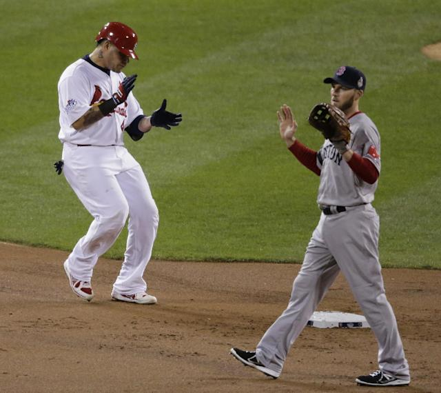St. Louis Cardinals' Yadier Molina reacts as he runs into second after hitting a double during the second inning of Game 4 of baseball's World Series against the Boston Red Sox Sunday, Oct. 27, 2013, in St. Louis. Boston Red Sox shortstop Stephen Drew waits for the throw from the right field. (AP Photo/Charlie Riedel)