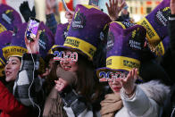 FILE - In this Dec. 31, 2019, file photo, revelers cheer as they wait in New York's Times Square to take part in a New Year's Eve celebration. If ever a year's end seemed like cause for celebration, 2020 might be it. Yet the coronavirus scourge that dominated the year is also looming over New Year's festivities and forcing officials worldwide to tone them down. (AP Photo/Adam Hunger, File)