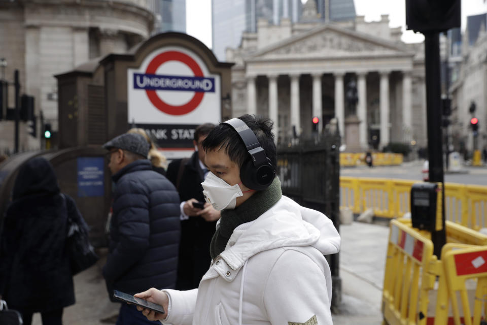 A man wearing a face mask walks past an entrance sign for Bank underground train station backdropped by the Royal Exchange building in London, Wednesday, March 4, 2020. British authorities laid out plans Tuesday to confront a COVID-19 epidemic, saying that the new coronavirus could spread within weeks from a few dozen confirmed cases to millions of infections, with thousands of people in the U.K. at risk of death. (AP Photo/Matt Dunham)