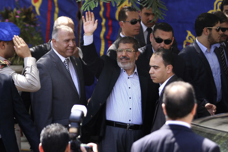 Egyptian President Mohammed Morsi, center, waves to worshippers ash he arrives for Friday prayers at Sayyeda Zainab mosque in Cairo, Egypt, Friday, Sept. 7, 2012. (AP Photo/Ahmed Ali)