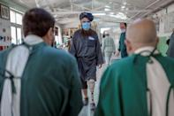 Mullah Yacoub (C), a Taliban member who claims to have lost his leg in an US strike, walks to try on his new prosthetic leg (AFP/BULENT KILIC)