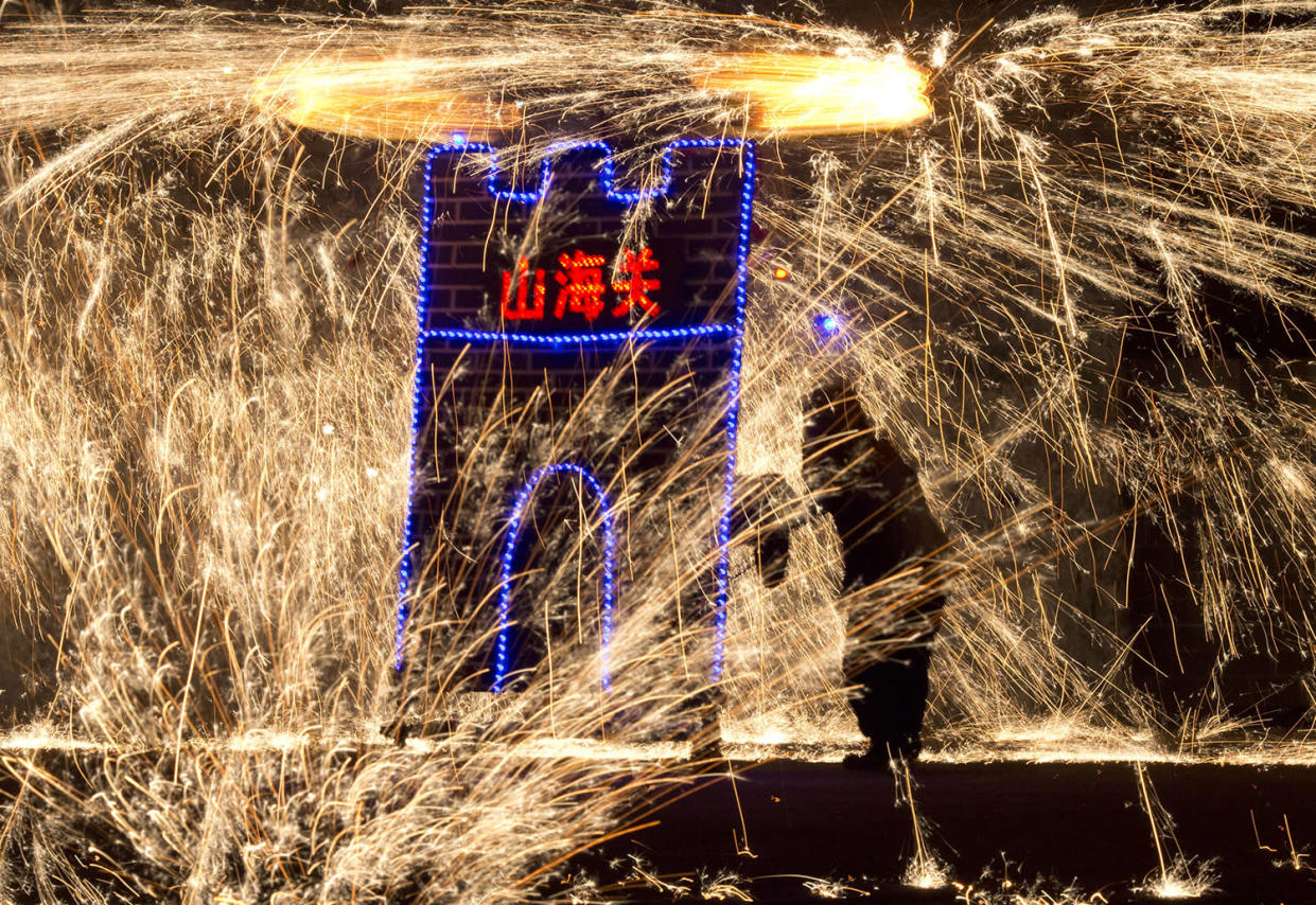 A performer at the Great Wall Iron Sparks show turns a mechanism to spin molten iron and create sparks in Yanqing county on the outskirts of Beijing, China, Saturday, Jan. 28, 2017. An ancient craft that can be traced back several hundred years, the company is trying to revive the practice of throwing the molten iron and using the Lunar New Year period to showcase their latest choreography. Chinese character reads