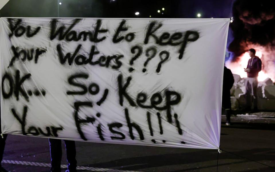 French fishermen hold a banner as they block lorries - Reuters