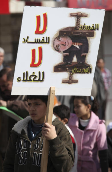 """A Jordanian boy holds a sign that reads in Arabic """"No for corruption and no for price hikes"""" during a protest by the Muslim Brotherhood movement and other opposition parties against the upcoming parliamentary elections, in Amman, Jordan, Friday, Jan. 18, 2013. Friday's peaceful demonstration drew about 1,300 Muslim Brotherhood members and others, united in the election boycott and in demands that King Abdullah II cede some of his powers and give parliament more say in the country. The demonstration comes just five days before elections that will for the first time see a prime minister emerge from among the winning candidates, rather than by appointment by the king. (AP Photo/Mohammad Hannon)"""
