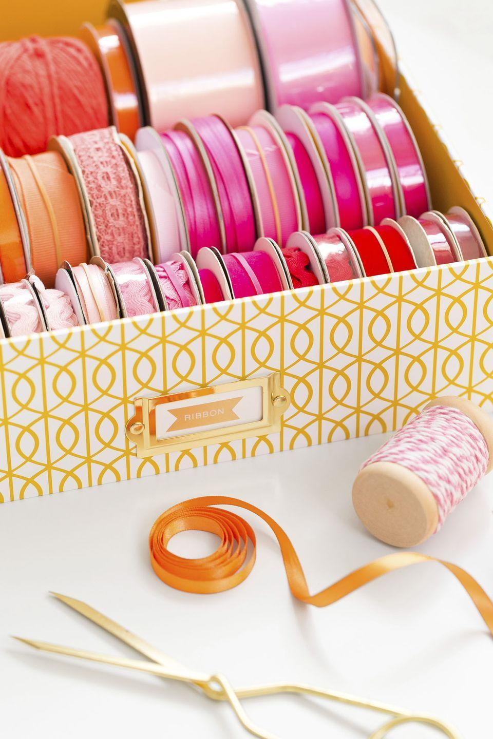 """<p>Unless you're an avid crafter, you probably don't bust out your ribbon stash on the daily. Before <a href=""""https://www.goodhousekeeping.com/holidays/gift-ideas/tips/g1775/diy-holiday-gift-wrap/"""" rel=""""nofollow noopener"""" target=""""_blank"""" data-ylk=""""slk:gift giving season hits"""" class=""""link rapid-noclick-resp"""">gift giving season hits</a>, set up a portable (and pretty!) ribbon station by placing the color-coordinated spools in a shallow box. When it comes to wrap, you can shop through your stash to find what you need. </p><p><a class=""""link rapid-noclick-resp"""" href=""""https://www.amazon.com/PHOTO-STORAGE-BOXES-HOLDS-PHOTOS/dp/B003WSV1RI/?tag=syn-yahoo-20&ascsubtag=%5Bartid%7C10063.g.36459111%5Bsrc%7Cyahoo-us"""" rel=""""nofollow noopener"""" target=""""_blank"""" data-ylk=""""slk:SHOP STORAGE BOXES"""">SHOP STORAGE BOXES</a> </p>"""