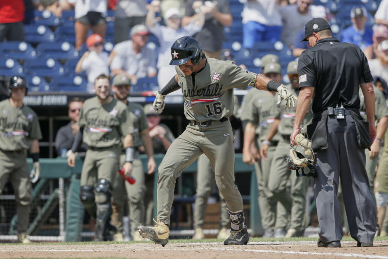 Vanderbilt's Austin Martin (16) stomps on home plate after hitting a two-run home run against Louisville in the seventh inning of an NCAA College World Series baseball game in Omaha, Neb., Sunday, June 16, 2019. (AP Photo/Nati Harnik)