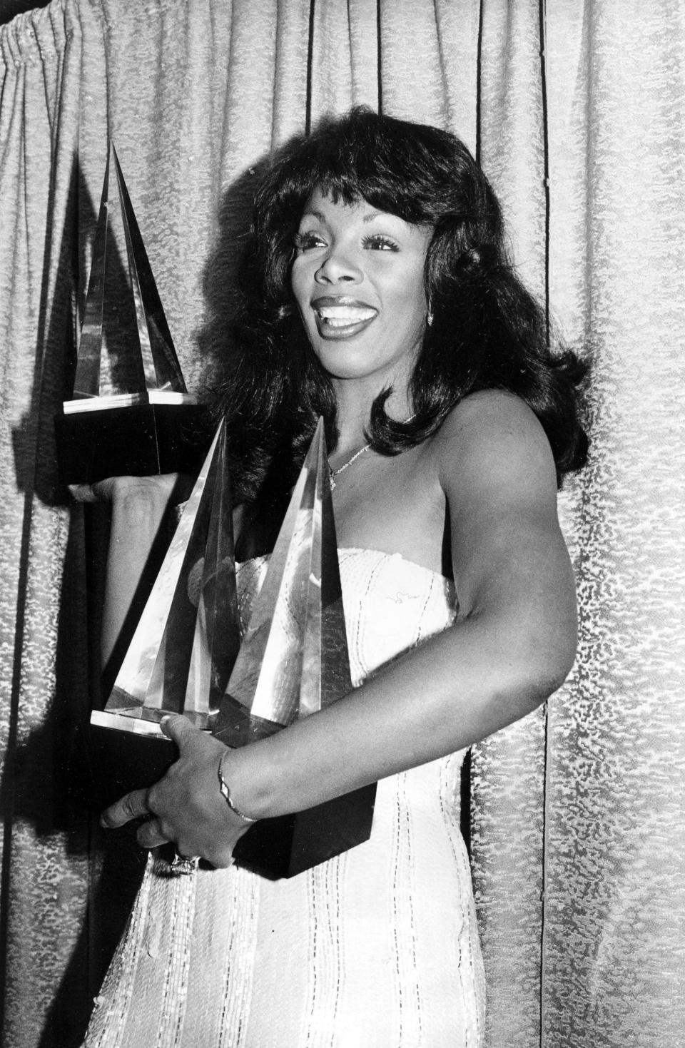 """FILE - In this Jan. 12, 1979 file photo, singer Donna Summer poses with three awards she won at the American Music Awards in Los Angeles, Calif. Summer, the Queen of Disco who ruled the dance floors with anthems like """"Last Dance,"""" """"Love to Love You Baby"""" and """"Bad Girl,"""" has died. Her family announced her death in a statement Thursday, May 17, 2012. She was 63. (AP Photo/Nick Ut, File)"""