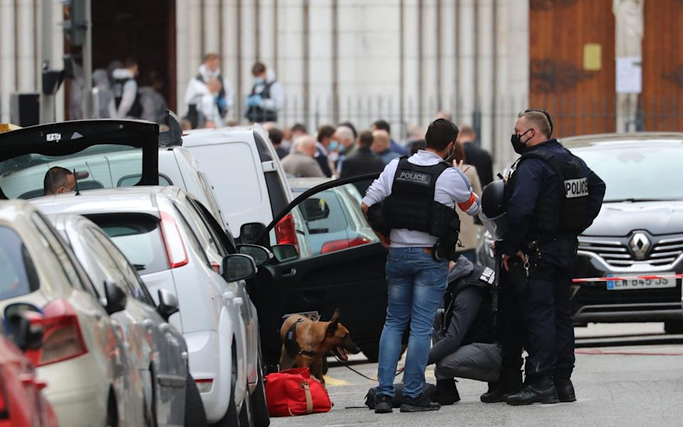 A police dog handler and officers search a car parked near the Basilica of Notre-Dame de Nice - VALERY HACHE /AFP