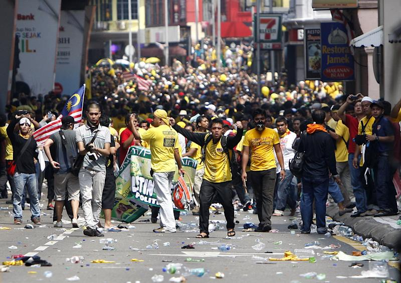 Protesters encounter Malaysian police, not in photo,  during a rally to demand for electoral reforms in Kuala Lumpur, Malaysia, Saturday, April 28, 2012. At least 25,000 demonstrators had swamped Malaysia's largest city in one of the Southeast Asian nation's biggest street rallies in the past decade. (AP Photo/Lai Seng Sin)