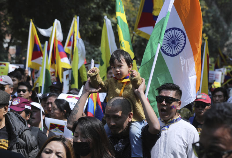 An exile Tibetan carries his son on his shoulder and participates in a march to mark the 60th anniversary of the March 10, 1959 Tibetan Uprising Day, in New Delhi, India, Sunday, March 10, 2019. The uprising of the Tibetan people against the Chinese rule was brutally quelled by Chinese army forcing the spiritual leader the Dalai Lama and thousands of Tibetans to come into exile. Every year exile Tibetans mark this day as the National Uprising Day. (AP Photo/Manish Swarup)