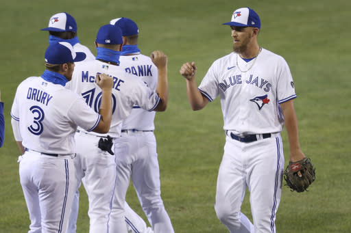 Toronto Blue Jays pitcher, right, celebrates a 12-4 victory over Tampa Bay Rays following the ninth inning of a baseball game, Friday, Aug. 14, 2020, in Buffalo, N.Y. (AP Photo/Jeffrey T. Barnes)