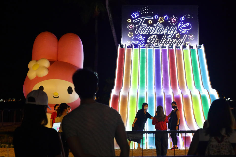 SINGAPORE - DECEMBER 16: People wearing protective mask takes a photo with a Sanrio character', My Melody during the Sentosa's festive light-up, Island Lights with Sanrio characters at Siloso beach, Sentosa on December 16, 2020 in Singapore. As of 16 December, the Ministry of Health confirmed 12 new imported COVID-19 cases with no cases in the wider community bringing the country's total to 58,353. (Photo by Suhaimi Abdullah/Getty Images)