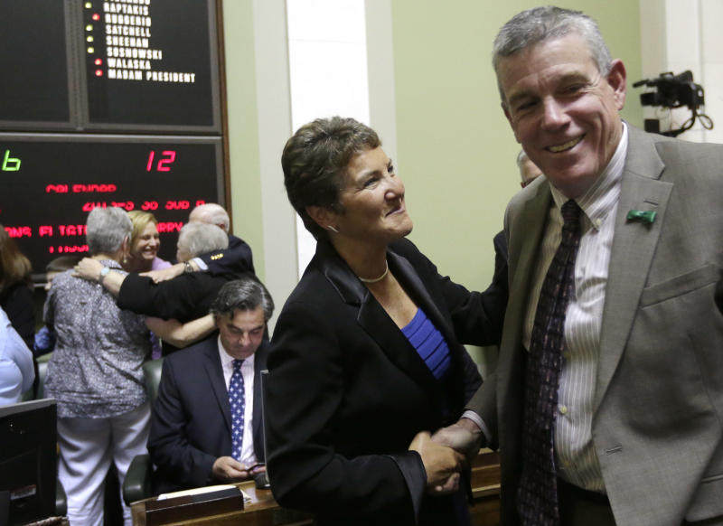 Rhode Island state Sen. Donna Nesselbush, D-Pawtucket, center, shakes hands with R.I. state Sen. Paul Fogarty, D-Glocester, moments after the state Senate passed a same-sex marriage bill at the Statehouse, in Providence, R.I., Wednesday, April 24, 2013. Nesselbush was the main sponsor of the bill in the Senate. (AP Photo/Steven Senne)
