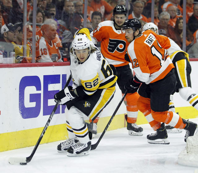 Pittsburgh Penguins' Carl Hagelin, left, skates away with the puck as Philadelphia Flyers' Scott Laughton, center, and Michbael Raffl, right, watch during the second period in Game 4 of an NHL first-round hockey playoff series Wednesday, April 18, 2018, in Philadelphia. (AP Photo/Tom Mihalek)