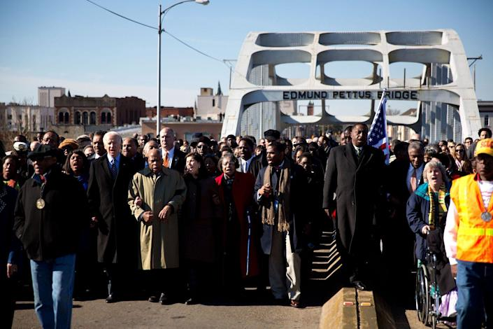 Biden marches arm in arm with Rep.Terri Sewell (D-Ala.) and civil rights legend and Rep. John Lewis (D-Ga.) across the Edmund Pettus Bridge during the 48th annual Bridge Crossing Ceremony in Selma, Alabama on March 3, 2013.