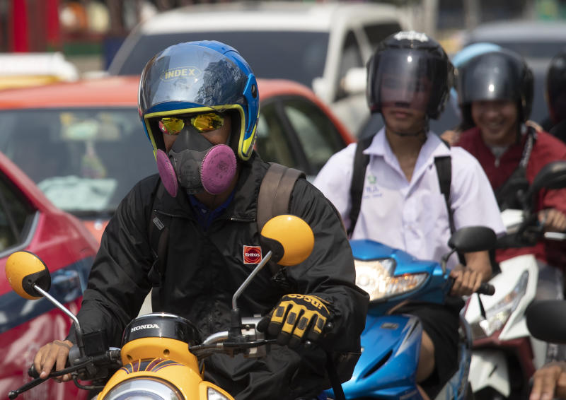 Motorcyclists wear face masks to protect from the poor air quality Bangkok, Thailand, Monday, Jan. 20, 2020. Thick haze blanketed the Thai capital on Monday sending air pollution levels soaring to 89 micrograms per cubic meter of PM2.5 particles in some areas, according to the Pollution Control Department. (AP Photo/Sakchai Lalit)