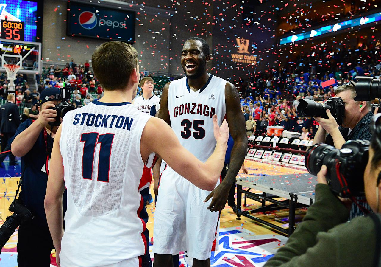 In this photo provided by the Las Vegas News Bureau, West Coast Conference All - Tournament stars David Stockton and Sam Dower Jr. of Gonzaga University celebrate their 75-64 victory over BYU in the conference championship game at The Orleans Arena in Las Vegas, Nevada. Tuesday March 11, 2014. (AP Photo/Las Vegas News Bureau, Steve Spatafore)