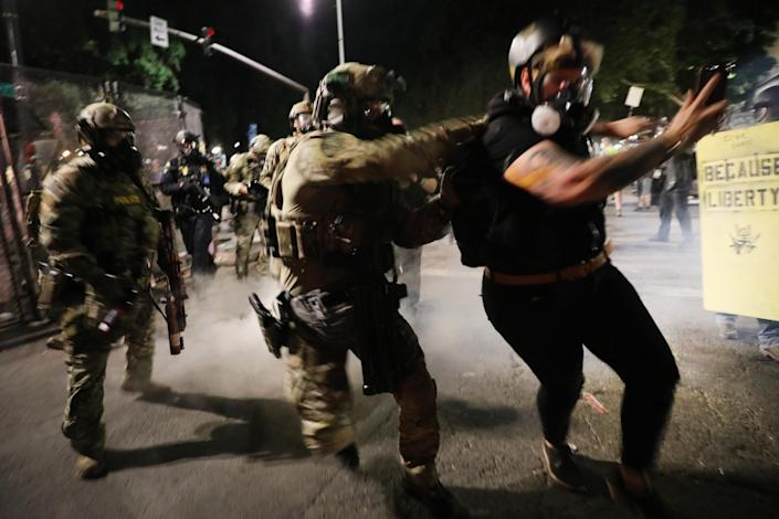Federal police make an arrest as they confront protesters Sunday night in Portland, Ore. (Spencer Platt/Getty Images)